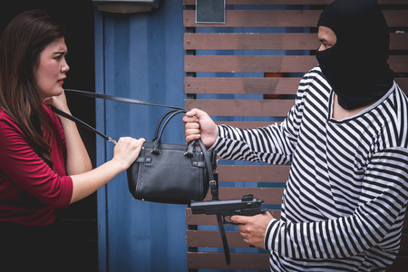 Thief threatening with gun, young woman fight over with robber who stealing bag.
