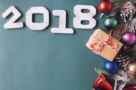 Houten nummers 2018 met Kerstdecoratie op groene achtergrond. Gelukkig Nieuwjaar concept. Vrije ruimte voor tekst
