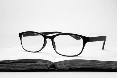 Oogglazen op een open boek, zwart-witte toon
