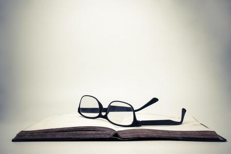 ヴィンテージの背景を持つオープンブック上の眼鏡。 写真素材