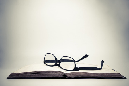 Eyeglasses on an open book with vintage background. Imagens