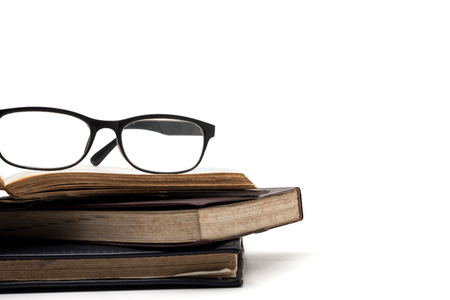 A stack of old books with eyeglasses on a white background.