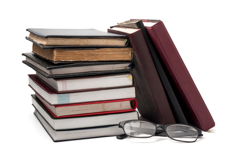 A stack of books with eyeglasses on a white background. Stock Photo