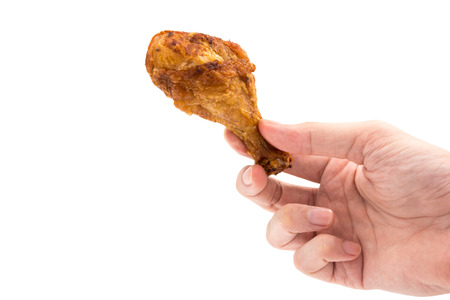 Hand holding Fried chicken leg on a white background.