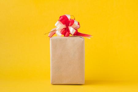 Paquetes de regalo envueltos en papel marrón con arco sobre fondo amarillo. Foto de archivo - 91938346