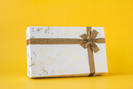 White gift box on a yellow background. Stock Photo