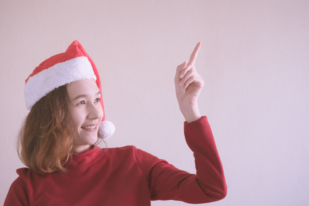 Portrait of Happy Asian woman dressed in red Christmas hat and red sweater.