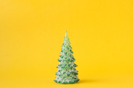 Christmas decoration with pine tree on yellow background.
