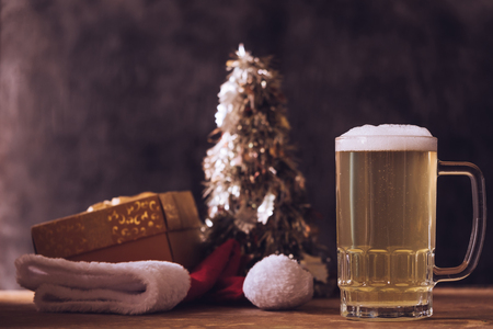 Mug of beer with Christmas decorations on the wooden table.