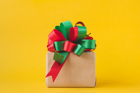 노란색 배경에 활과 갈색 종이에 싸서 선물 패키지.