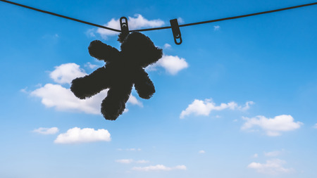 Silhouette of Teddy bear hanging on the clothes line with blue sky.