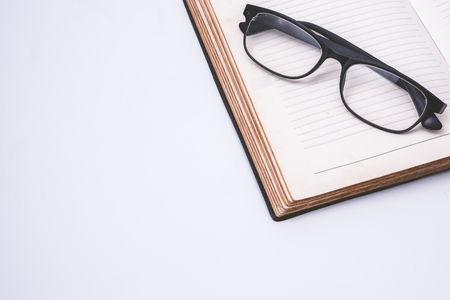 An open notebook with glasses on white background. Free space for text Stock Photo