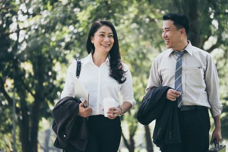 Feliz hombre de negocios asiático y mujer caminando y hablando en el parque público después de terminar el trabajo. Foto de archivo