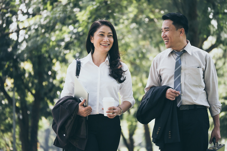 Happy Asian business man and woman walking and talking in the public park after finish work. Banque d'images