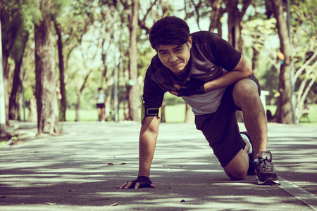 An Asian man has a heart pain while exercising in a park. Archivio Fotografico