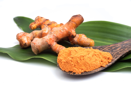Turmeric roots with turmeric powder on green leaf over white background. Banque d'images