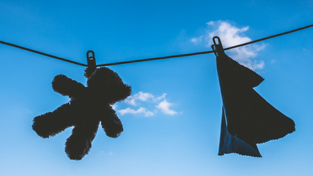 Silhouette of Teddy bear and napkin hanging on the clothes line with blue sky.