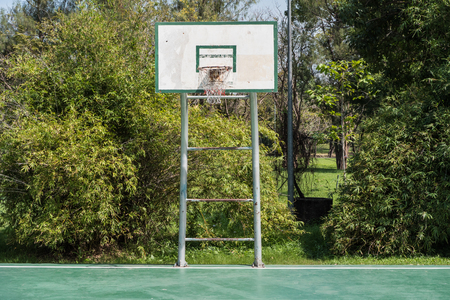 A backboard on basketball court in a park.