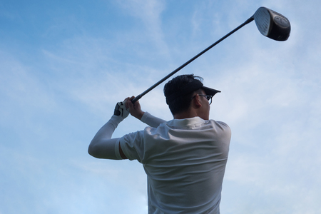 Portrait of asian young male golfer with golf club on blue sky background.