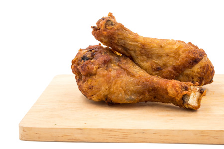 Fried chicken legs on wooden tray over a white background.