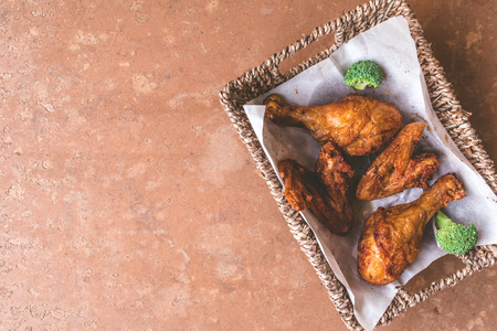 Top view of Fried chicken legs and wings in basket. Free space for text