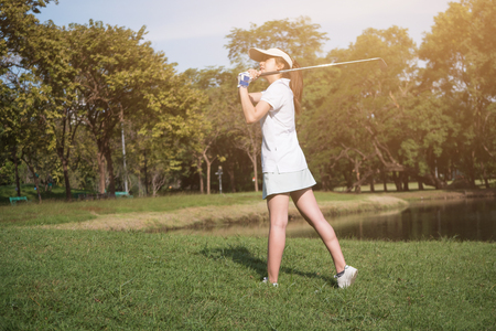 Asian woman golf player swinging driver golf club on golf course. 版權商用圖片 - 92931721