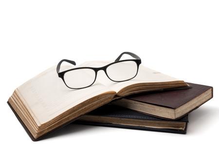 白い背景に眼鏡をかけた古い本の山。