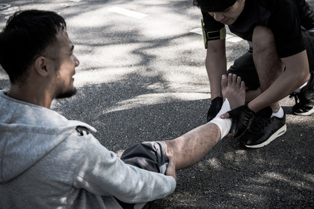 A man uses elastic bandage for pain relief one man's ankle after a workout in a park. Banque d'images