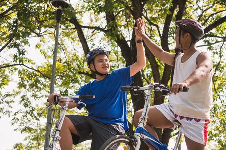 友人は、一緒に曇った公園で一緒にサイクリングしながら、一緒に手を触れています。