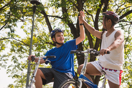 Friends are touching hands together while cycling together in a shady park.
