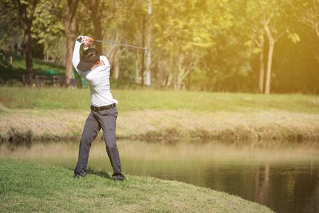ゴルフコースでアジアの男のゴルフ選手スイングドライバーゴルフクラブ。
