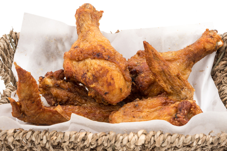 Fried chicken legs and wings in basket on a white background.