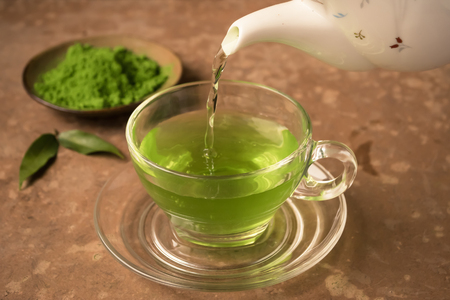 Green tea being poured into glass tea cup on the table Imagens