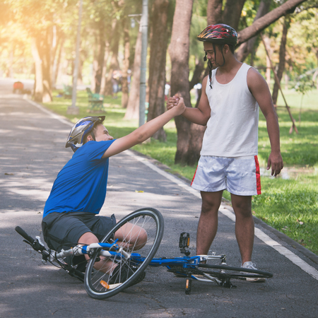 A young man helps his friend who get bicycle accident on a path. Stockfoto