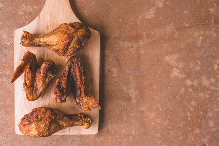 Top view of Fried chicken legs and wings on wooden tray. Free space for text