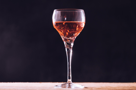Glass of wine on the wooden table, black background.