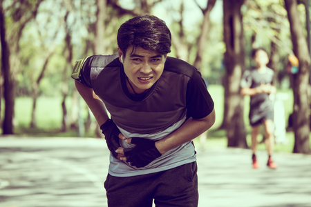 An Asian man has a stomachache while exercising in a park.