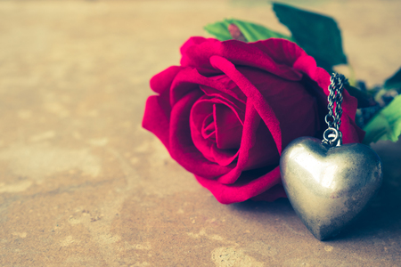 Red rose with silver heart necklace on brown grunge board background. Concept of Valentine Day. Vintage tone