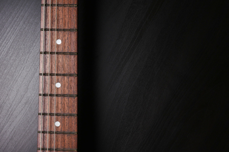 Close up of Electric guitar neck fingerboard on a black background. Free space for text Stock Photo