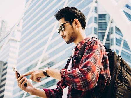 O homem asiático do viajante está andando na rua da cidade e está olhando lugares interessantes para viajar do telefone esperto. Férias e tecnologia conceito.