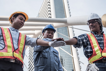 Architect, civil engineer and worker joining hands together with construction site background. Success and teamwork concept.