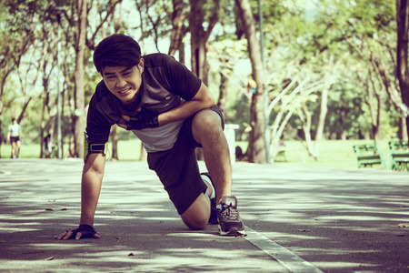 An Asian man has a heart pain while exercising in a park. Stockfoto