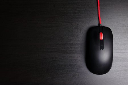 Black computer mouse on dark background. Free space for text