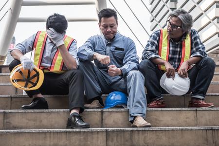 Der unglückliche Ingenieur, der auf Gebäudetreppen an der Baustelle sitzt, fühlen sich müde und von der Arbeit betont. Standard-Bild
