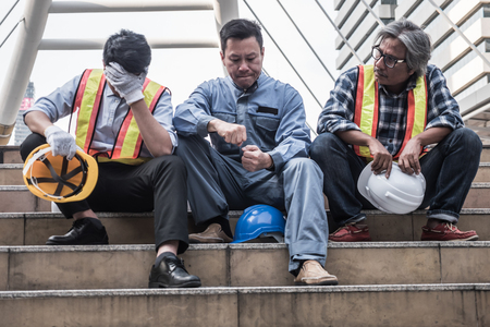 Unhappy engineer sitting on building stairs at construction site, They feel tired and stressed from work. 版權商用圖片 - 94922991
