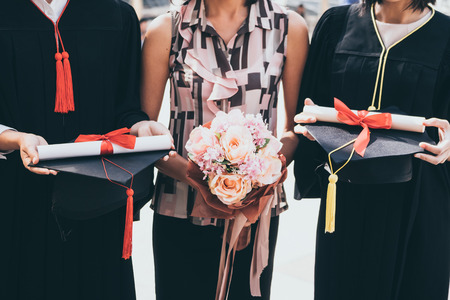 A woman with bouquet congratulates for her family on graduation day, Successful concept