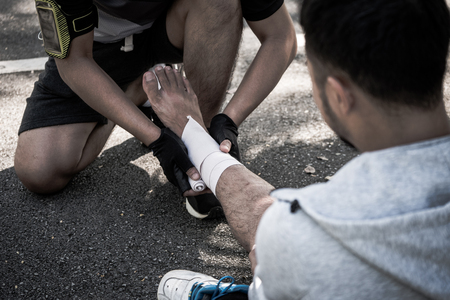 A man uses elastic bandage for pain relief one mans ankle after a workout in a park.