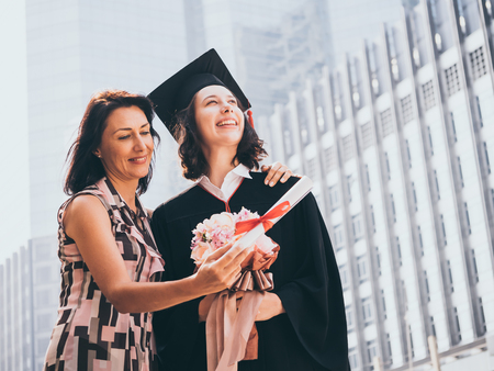 Beautiful woman congratulates for her daughter on graduation day, Successful concept 스톡 콘텐츠