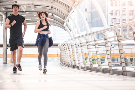 Young runners running on city bridge, Sporty couple jogging at morning with Bangkok urban scene background
