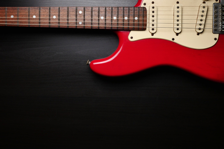 Close up of Electric guitar body and neck detail on black background.